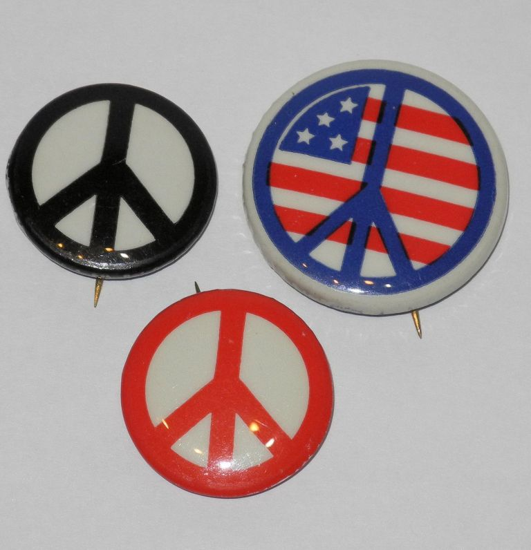 [Three peace sign pinback buttons]