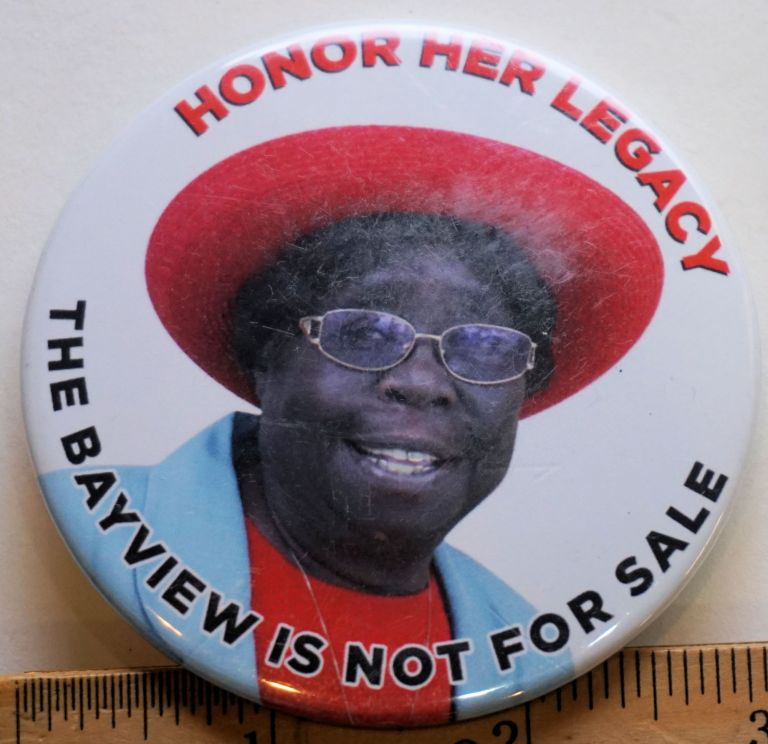 Honor Her Legacy; The Bayview is not for Sale [3-inch pinback button with text in red and black on a colorphoto field (activist in a red hat and skyblue coat)]