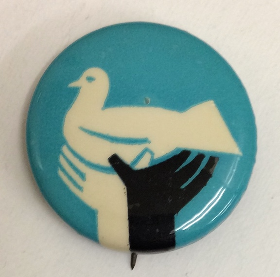 [Pinback button depicting black and white hands holding up a dove]
