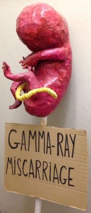 Gamma-ray miscarriage [protest sign with papier maché sculpture in form of a fetus