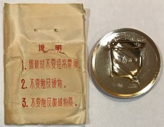 [Chairman Mao pin with original protective paper sleeve]