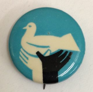 Pinback button depicting black and white hands holding up a dove